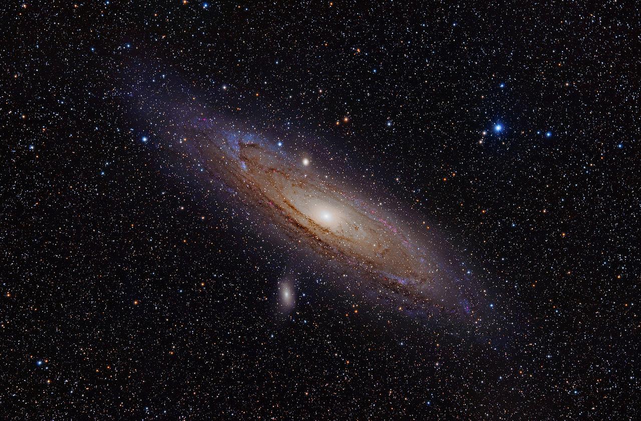 Nádherný pohľad na Veľkú hmlovinu v Androméde. Zhruba takto by vyzerala naša Galaxia aj s Magellanovými mrakmi pri pohľade zvonku. Stred je sfarbený do žlta, lebo obsahuje staršie žlté, oranžové a červené hviezdy. Naproti tomu ramená majú výraznú modrú farbu mladých hviezd. Tmavé oblasti sú mračná medzihviezdneho plynu a prachu. Všetky jednotlivé hviezdy v zábere ležia samozrejme omnoho bližšie a patria našej Galaxii.