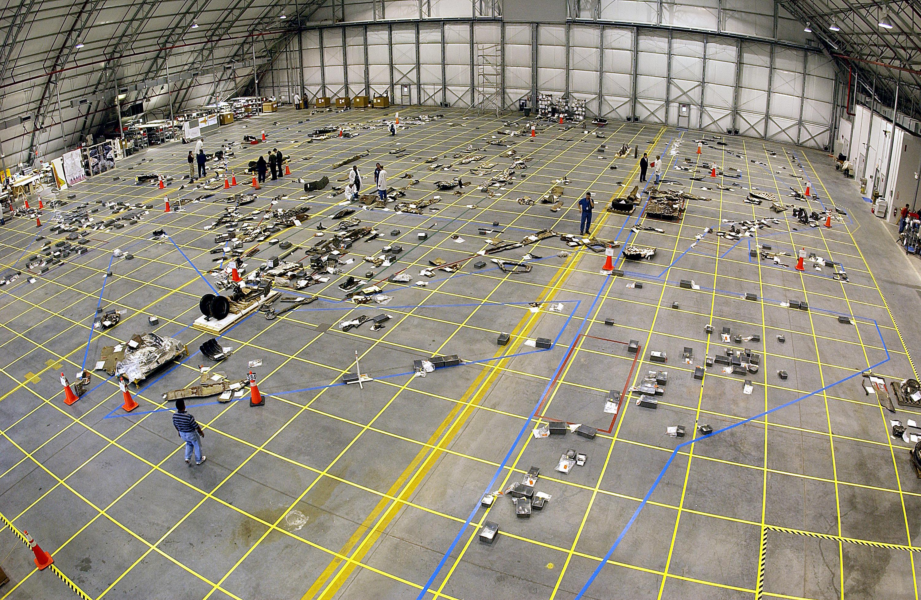 Umiestňovanie trosiek raketoplánu na vyznačené pozície na veľkom nákrese na podlahe hangáru. Na tomto obrázku je to umiestňovanie trosiek Columbie, ktorá havarovala vo februári 2003. Zdroj.