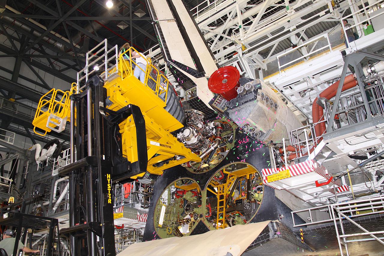 Scénu, kde Watson kontroluje motorovú sekciu raketoplánu Endeavour, ilustruje táto snímka. Aj na nej je Endeavour, do ktorého sa práve technici chystajú vmontovať prvý z troch motorov SSME, hlavných štartovacích motorov stroja. Viditeľné sú otvory, do ktorých budú motory vložené. Zdroj.