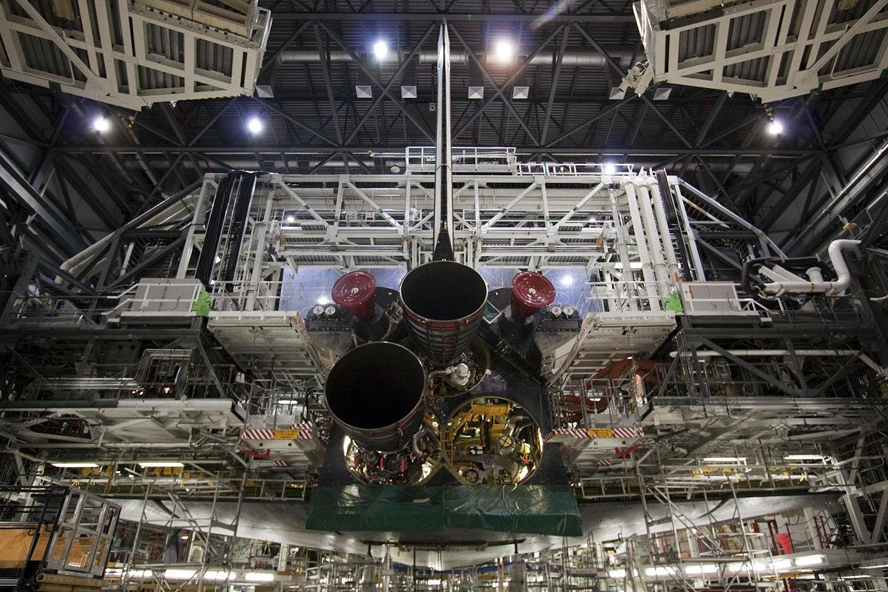 A ešte raz inštalácia motorov SSME. Lešeniami obložený Atlantis, ktorému zatiaľ chýba pravý spodný motor. Zdroj.
