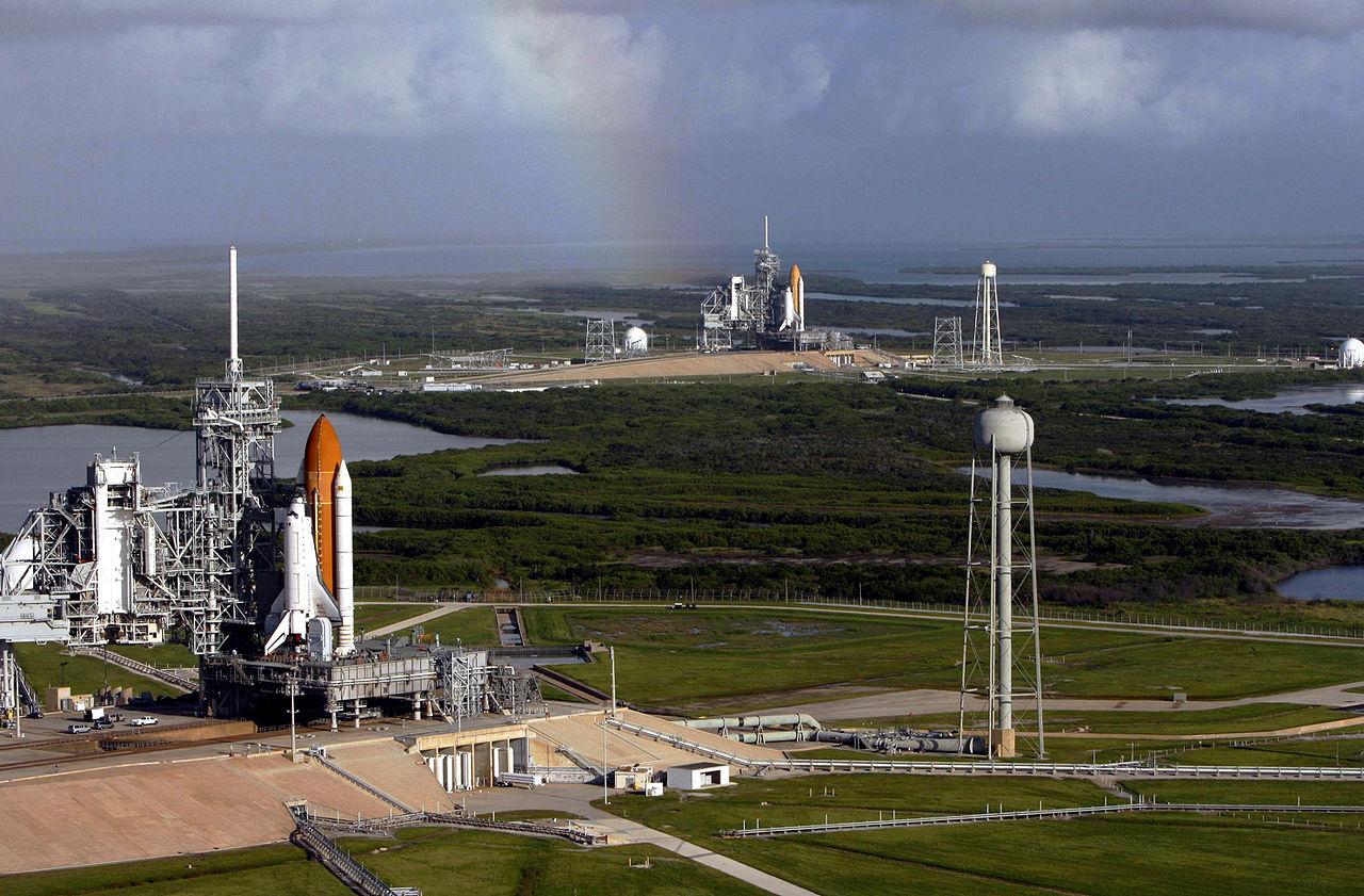 Štartovací komplex 39. Rampa 39-A, z ktorej mal v románe vzlietnuť Discovery, je v popredí – na tejto snímke ju okupuje raketoplán Atlantis. V pozadí je identická rampa 39-B s raketoplánom Endeavour. Zdroj.