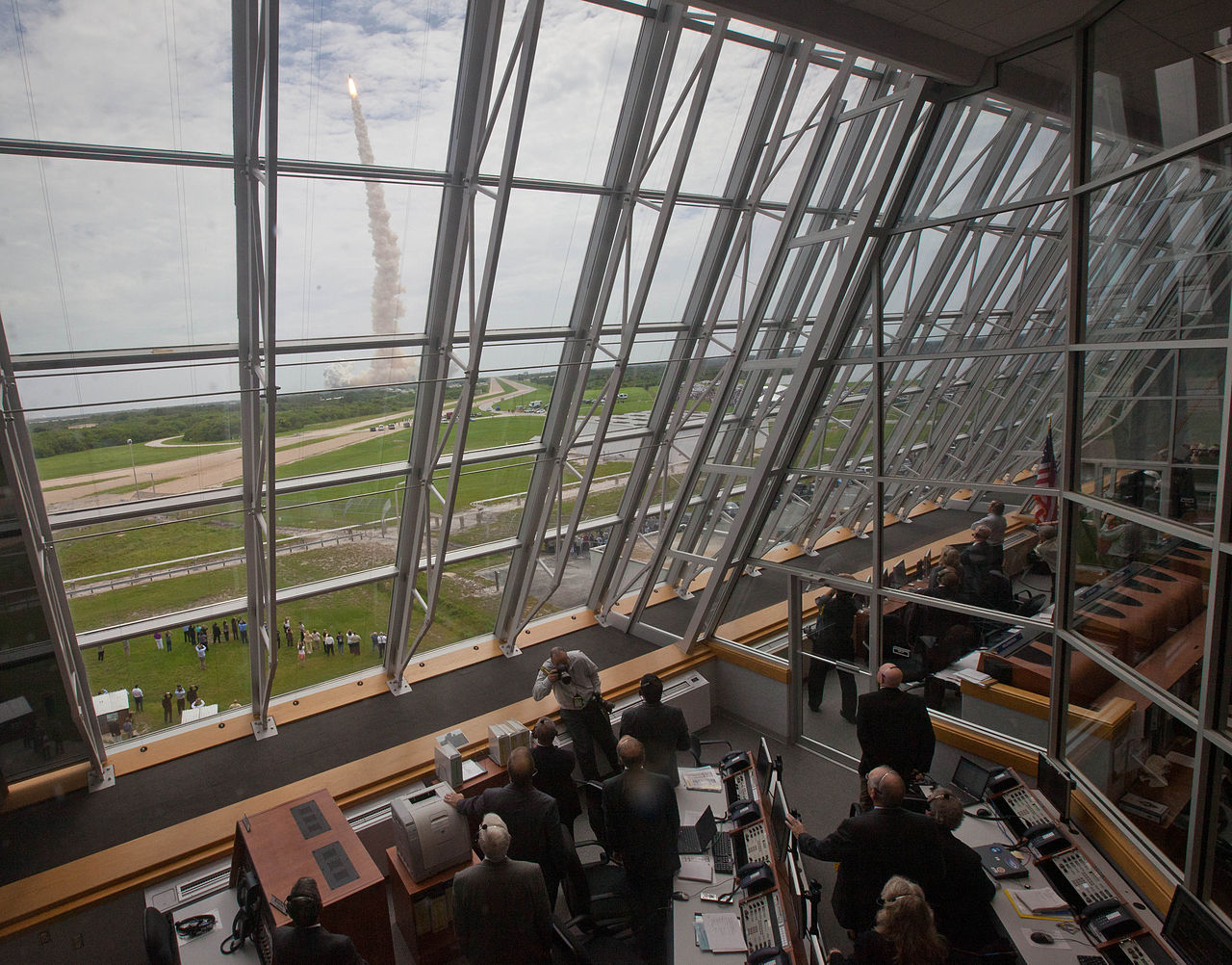 Stredisko riadenia štartu. Toto je spomínaná presklená stena, z ktorej bol nádherný výhľad na rampu. Na snímke momentálne vidieť, ako sa z nej dvíha raketoplán Atlantis. Zdroj.