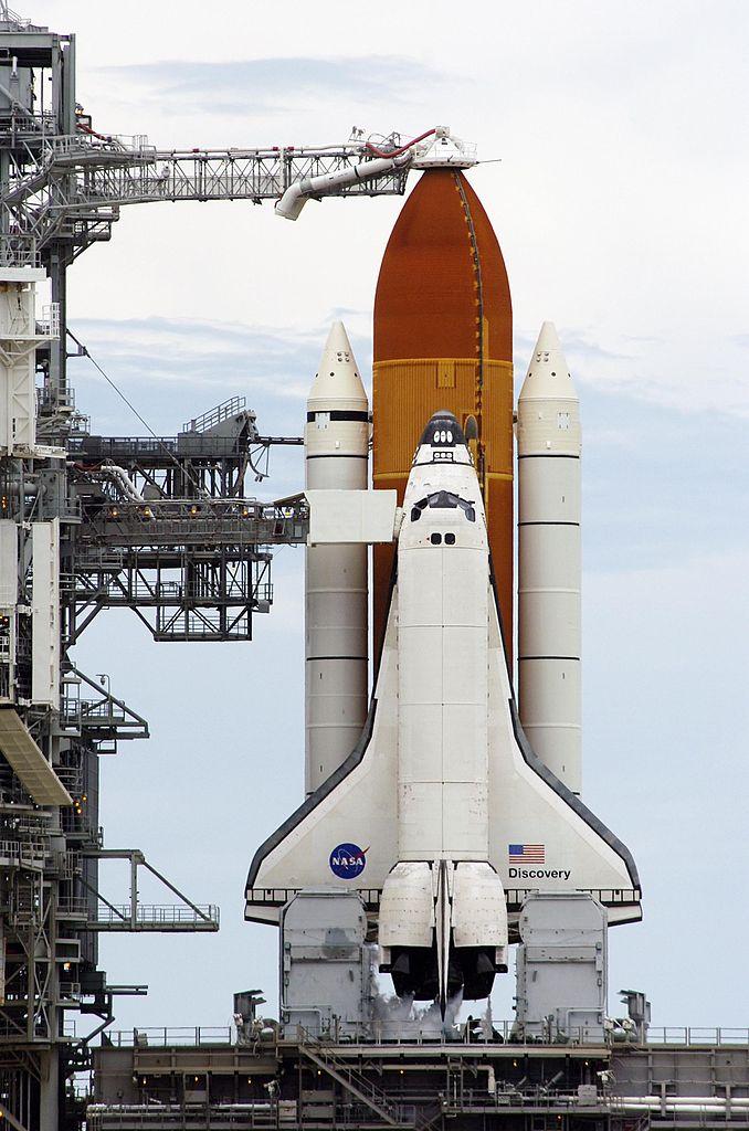 Discovery pred štartom z čelného pohľadu. Vlastný raketoplán (orbiter) je pripevnený k oranžovej nádrži ET, ktorá ho prevyšuje. Biele motory po bokoch pripomínajúce ceruzky sú motory SRB. Zdroj.