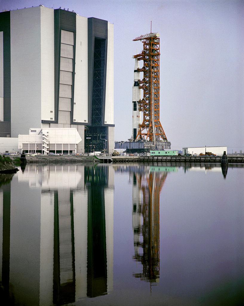 Najväčšia raketa sveta, Saturn V, ktorej názov (a nielen ten) sa stal inšpiráciou pre fiktívnu raketu Tachyon V. Saturny, rovnako ako aj Tachyony, sa presúvali na obrovských pásových prepravníkoch už vo vztýčenej podobe. Niečoho takéhoto bol Watson na začiatku roka svedkom. Zdroj.
