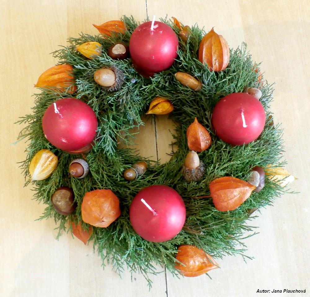 Tujový veniec v jesennom štýle. Jeho dominantou sú plody mochyne, obsahuje však aj šišky, gaštany, žalude. Vianočnú fasádu mu dodáva práškový lesk.